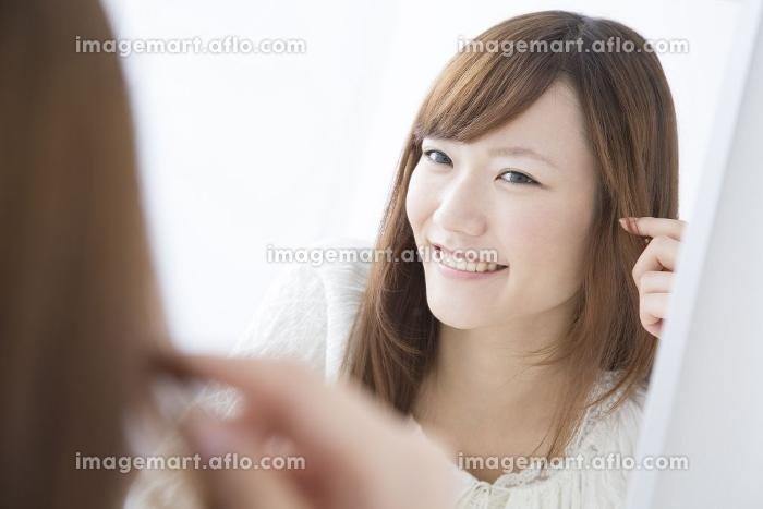 髪の毛をチェックする女性の販売画像