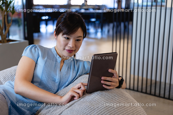 Front view of an Asian businesswoman wearing smart clothes, working in a modern office, sitting on a bean bag and using her tablet.の販売画像