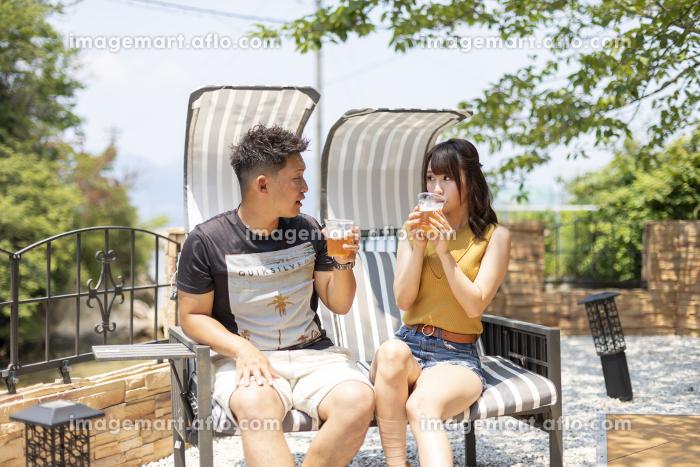 別荘の庭でビールを飲むカップルの販売画像