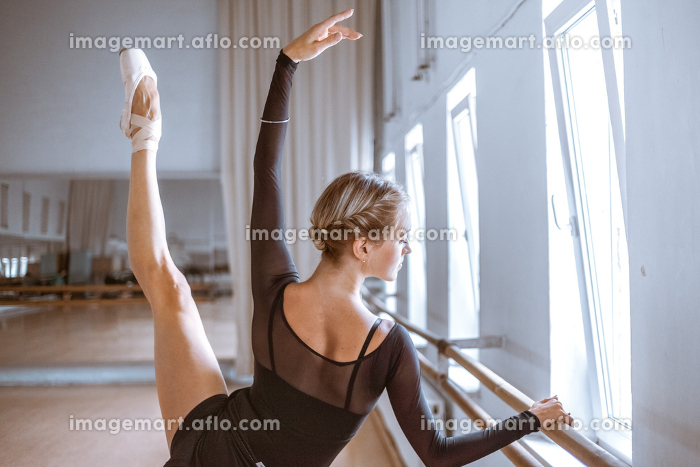 The young modern ballet dancer posing against the room backgroundの販売画像