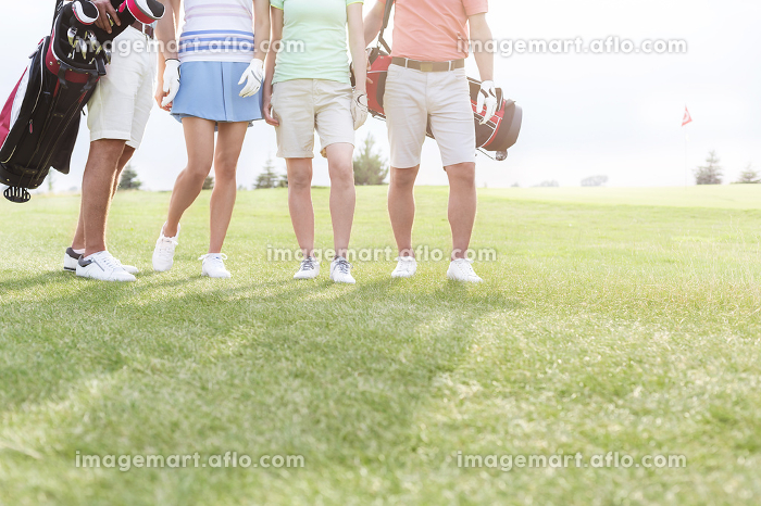 Low section of friends standing at golf courseの販売画像