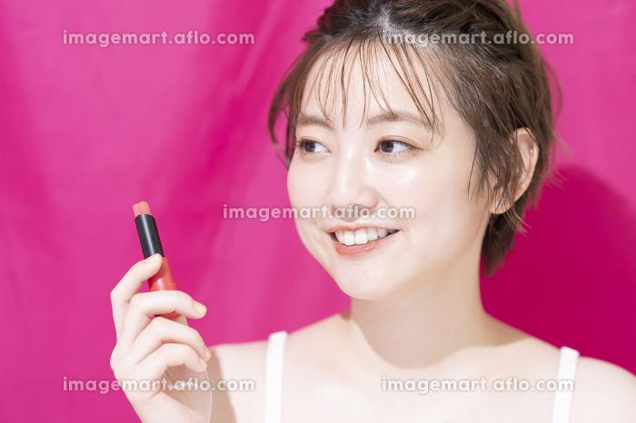 口紅を塗るアジア人の若い女性の販売画像