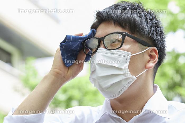 汗を拭く日本人ビジネスマンの販売画像