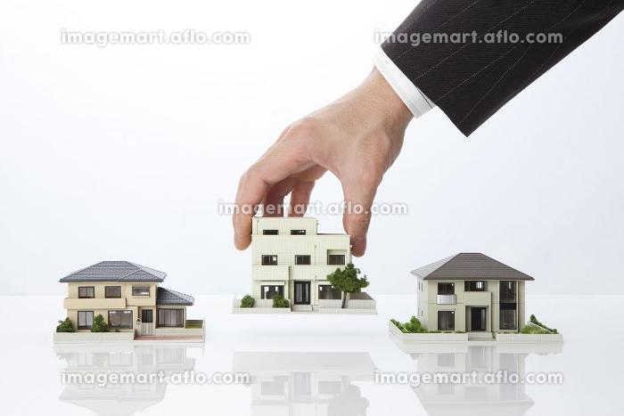 住宅模型を持つビジネスマンの販売画像