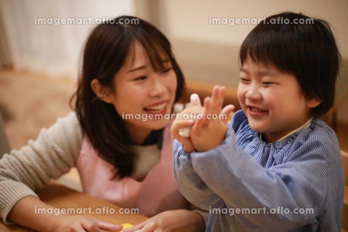 ねんどで遊ぶ男の子と保育士イメージの販売画像