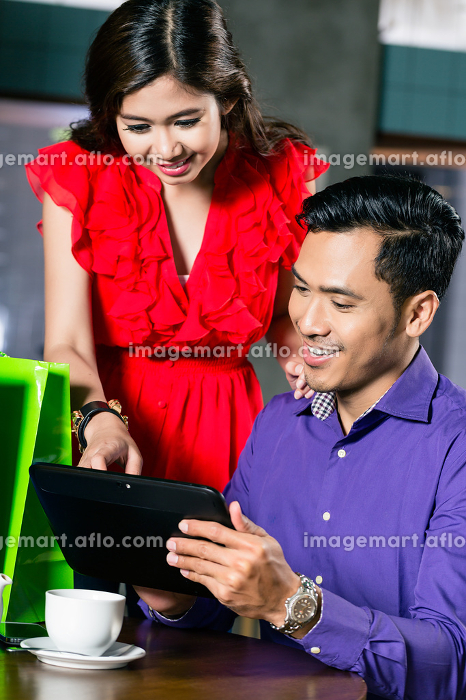 Young couple watching a funny video on a tablet connected to the internetの販売画像