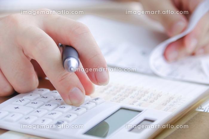 電卓で計算する女性の販売画像