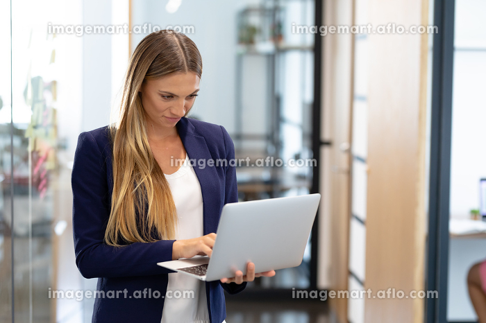 Smartly dressed caucasian businesswoman standing in corridor using laptop computer. business in a modern office.の販売画像