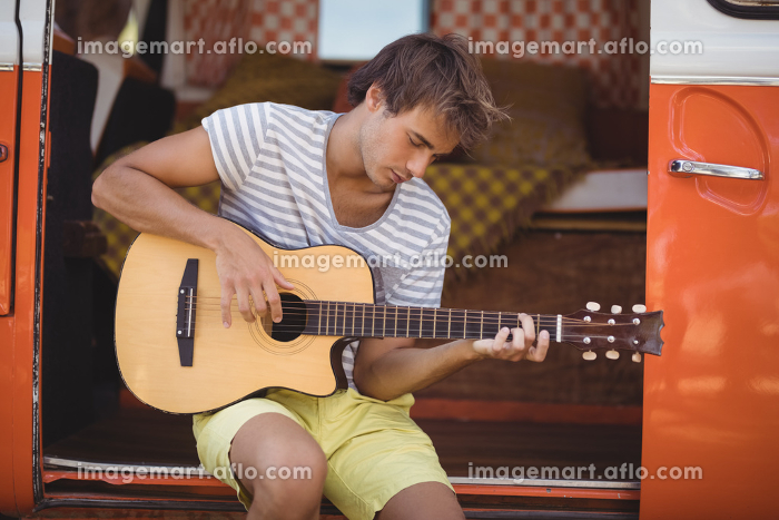 Young man playing guitar while sitting in motor homeの販売画像