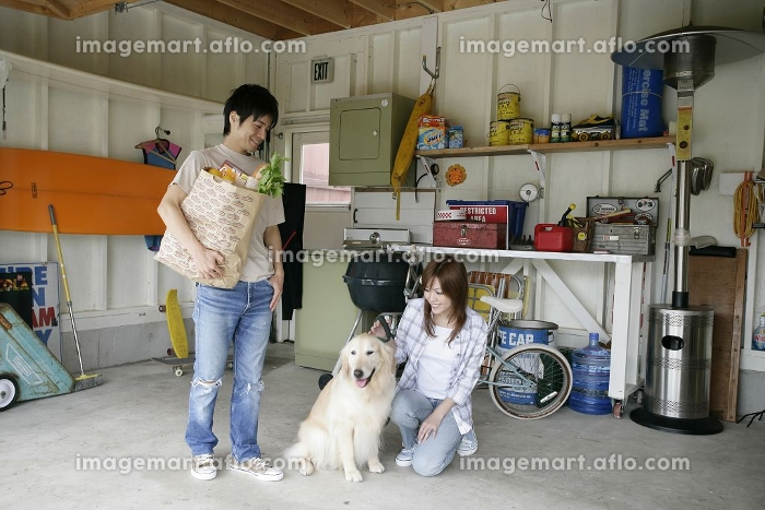 ガレージで犬を見つめるカップル