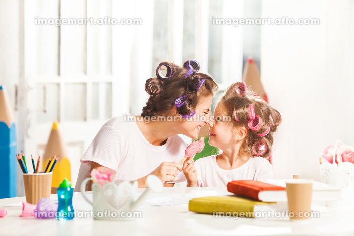 Little girl sitting with her mother and eating ice creamの販売画像