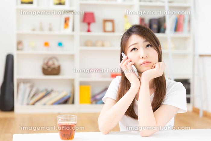 部屋で電話をする女性 考えるの販売画像