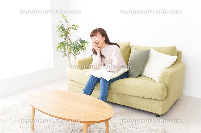 自宅でリラックスをする若い女性の販売画像