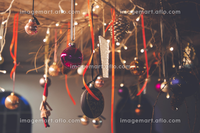 Christmas decoration hanging from a ceiling in a rural barn with xmas baubles and ribbons