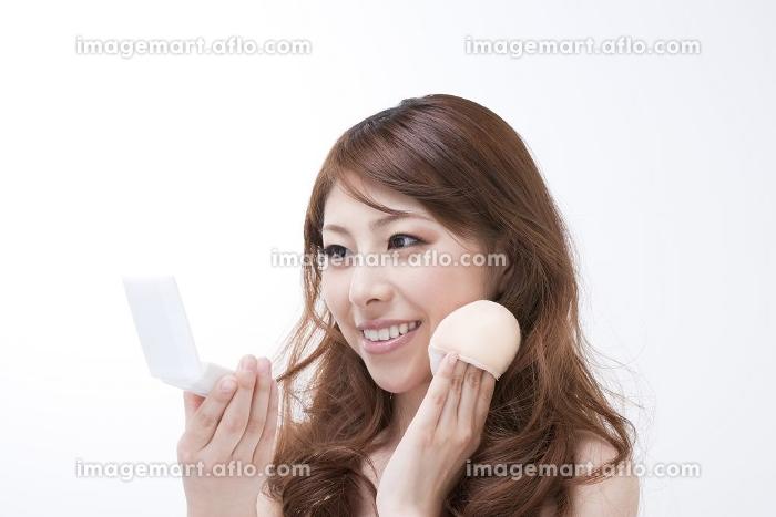 ファンデーションを塗る女性の販売画像