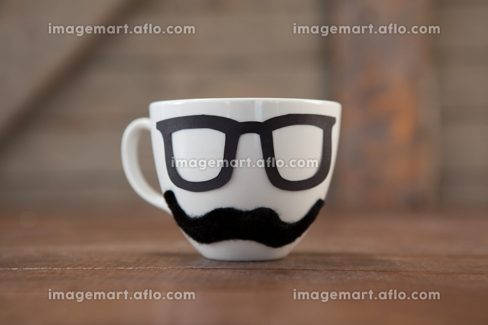 Fake moustache and spectacles on cup