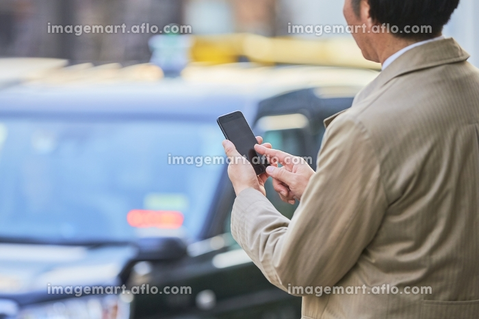 路上でスマホを操作する男性の販売画像