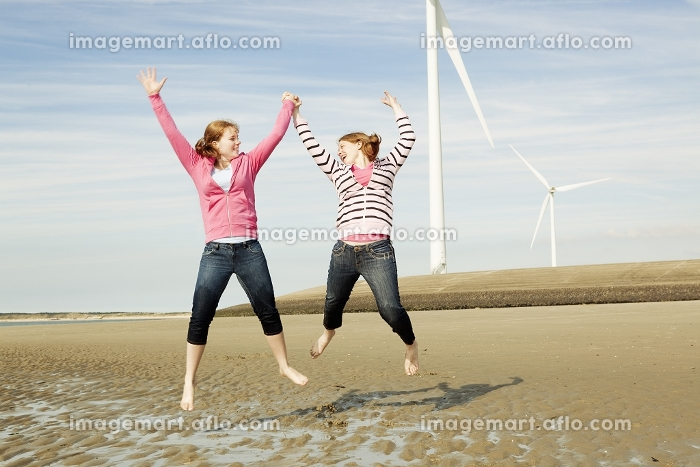 Two girls jumping on beach with turbinesの販売画像