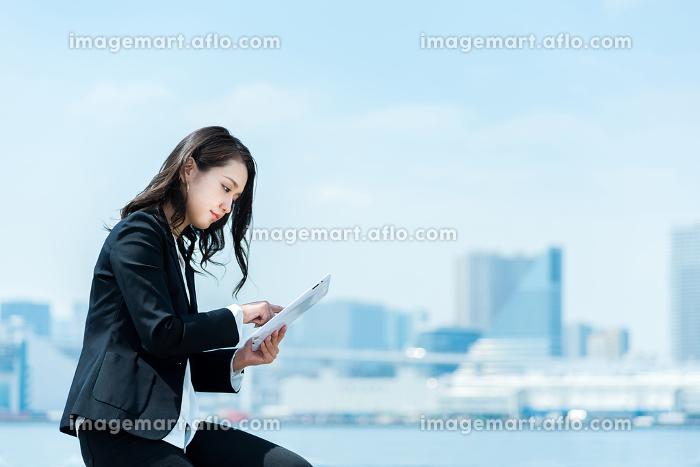 タブレットPCを使う女性・ビジネスイメージの販売画像