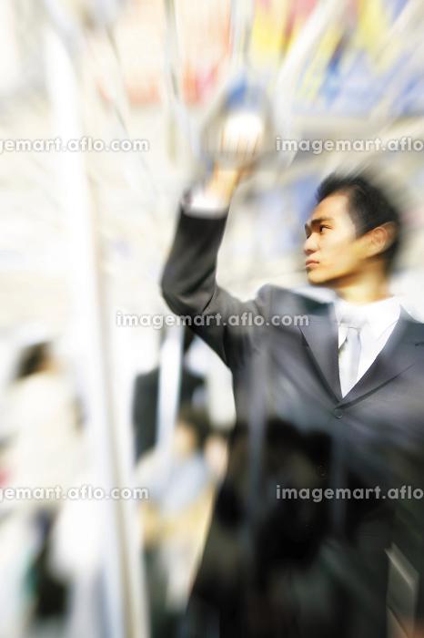 電車の吊り輪に掴まるビジネスマンの販売画像
