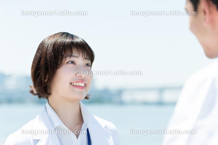 向かい合って話す女性(白衣の医者・医療従事者のイメージ)の販売画像