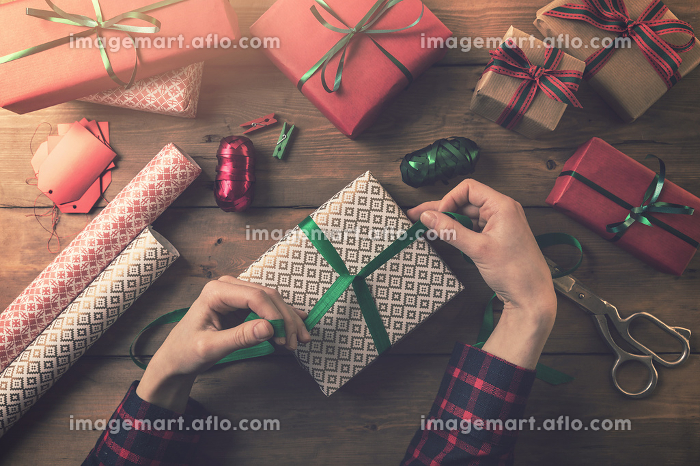gift wrapping. woman tie a ribbon bowの販売画像