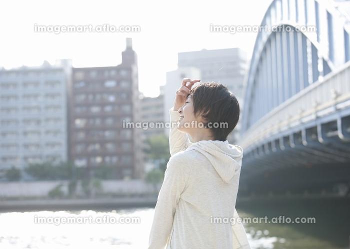 川沿いに立つ若い女性の販売画像