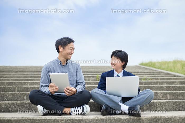 タブレットとPCを見ている日本人親子