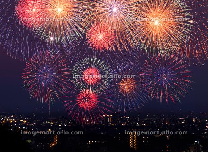夜の町並みに打ち上がる花火のイメージの販売画像
