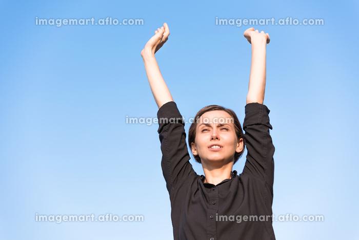 青空の下でリラックスをする若い女性の販売画像