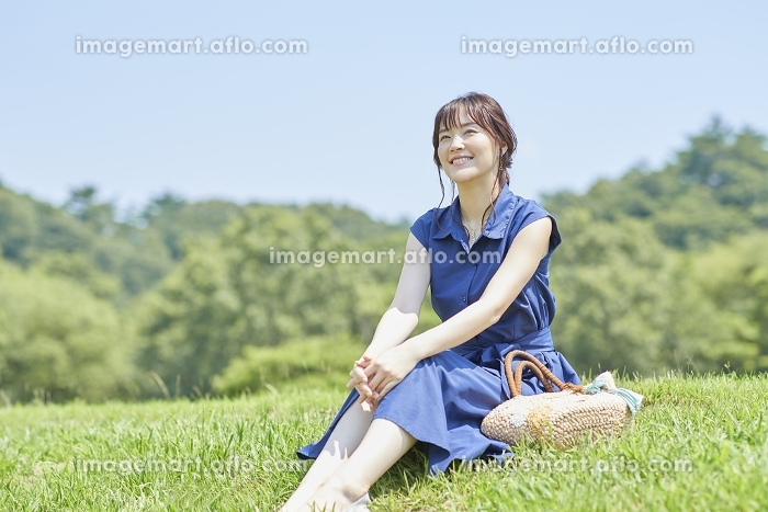 芝生の上でくつろぐ日本人女性の販売画像