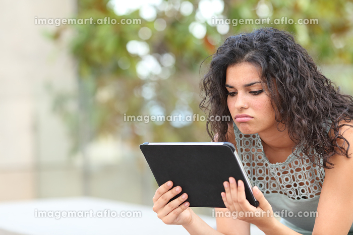 Bored woman watching media in a tablet in a parkの販売画像