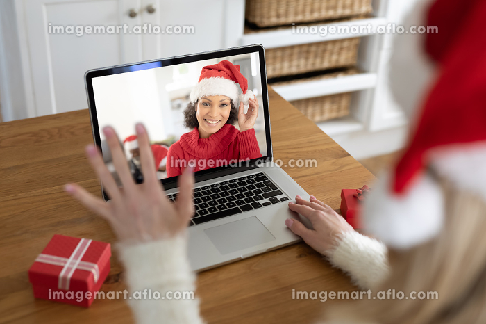 Caucasian woman spending time at home at Christmas, using laptop computer, video chatting with another woman and waving. Social distancing during Covid 19 Coronavirus quarantine lockdown.の販売画像