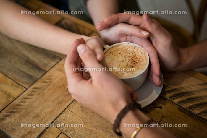 Couple holding hands and coffee cup in cafeteriaの販売画像