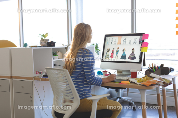 Rear view of young Caucasian blonde female fashion designer using graphic tablet while working at desk in a modern officeの販売画像