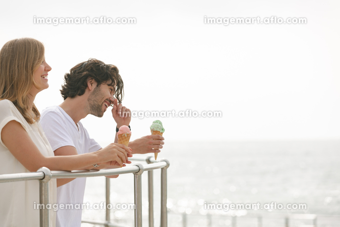 Side view of happy young Caucasian couple standing at promenade while having ice cream cone. They are smilingの販売画像