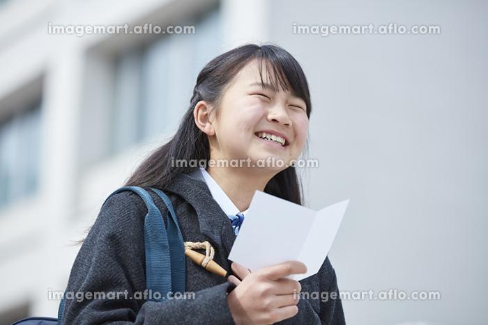 受験票を持って喜ぶ女子中学生の販売画像