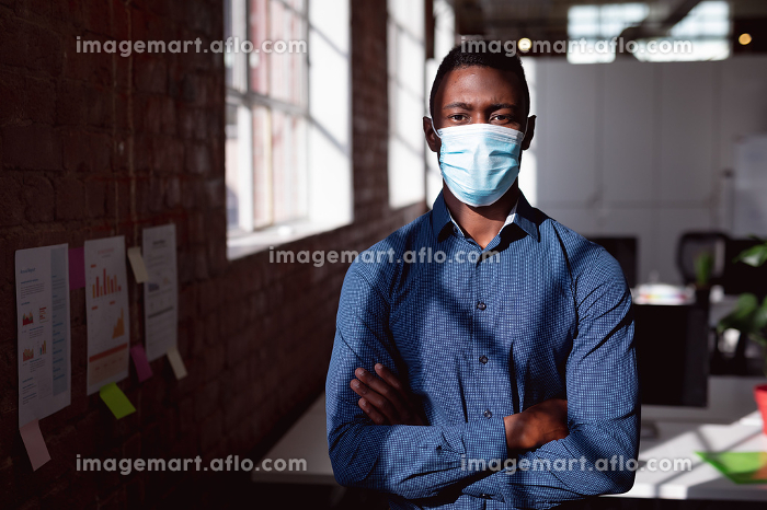 Portrait of african american businessman in face mask standing in office with arms crossed. working in business at a modern office during coronavirus covid 19 pandemic.の販売画像
