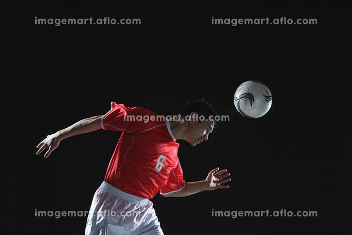 ヘディングシュートをするサッカー選手
