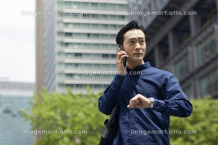 携帯電話で通話する日本人男性のポートレートの販売画像