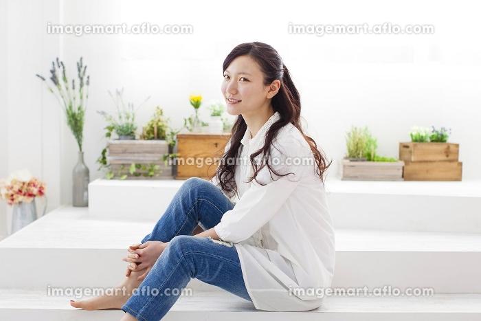 室内で座ってくつろぐ女性の販売画像