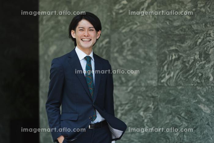 出社する若い男性・マンションのロビー背景・ビジネスイメージの販売画像