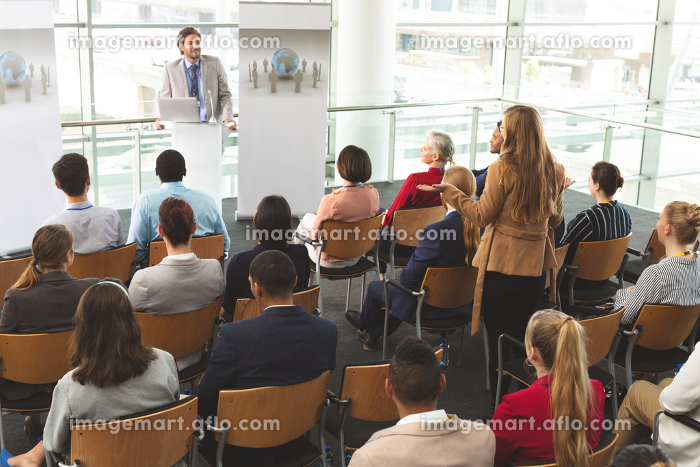 High angle view of Caucasian businesswoman interacting with Caucasian businessman speaking in front of business people sitting at business seminar in modern office buildingの販売画像