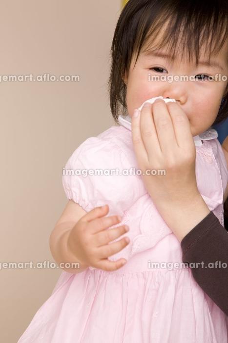 母親に鼻水を拭いてもらっている赤ちゃんの販売画像