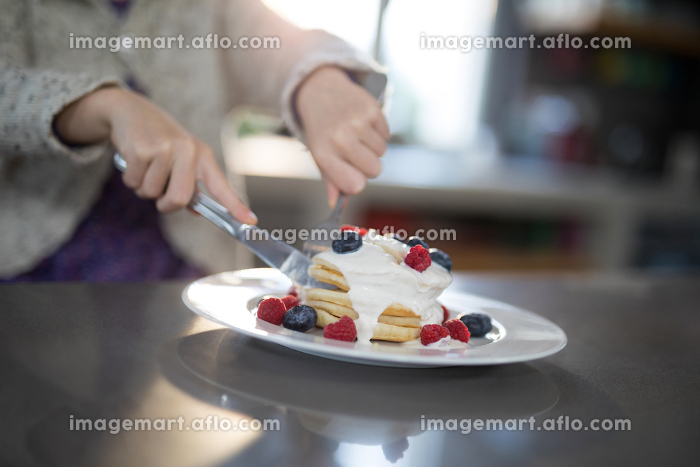 Little girl cutting a fruit pancake with a fork and knife