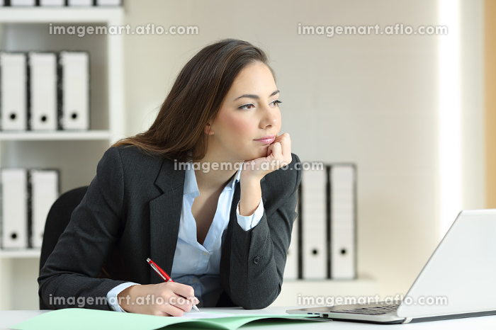 Businesswoman thinking looking away at officeの販売画像