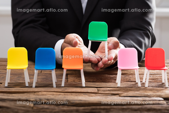 Businessperson's hand picking up green chairの販売画像