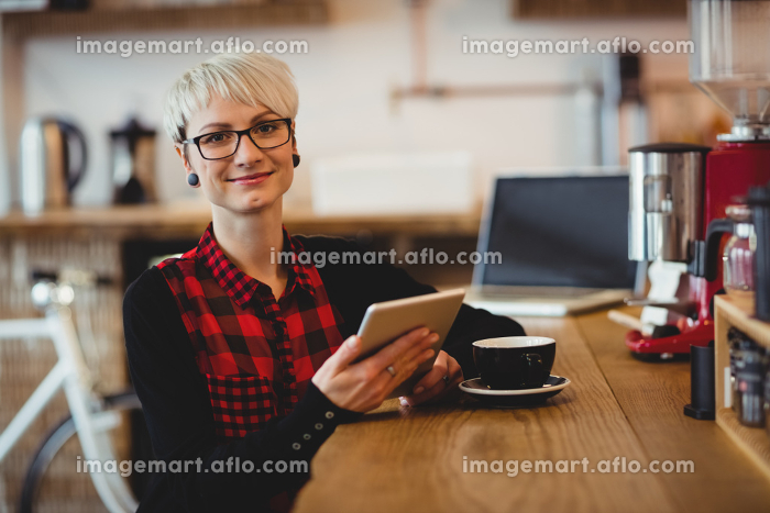 Young woman using digital tablet at office cafeteriaの販売画像