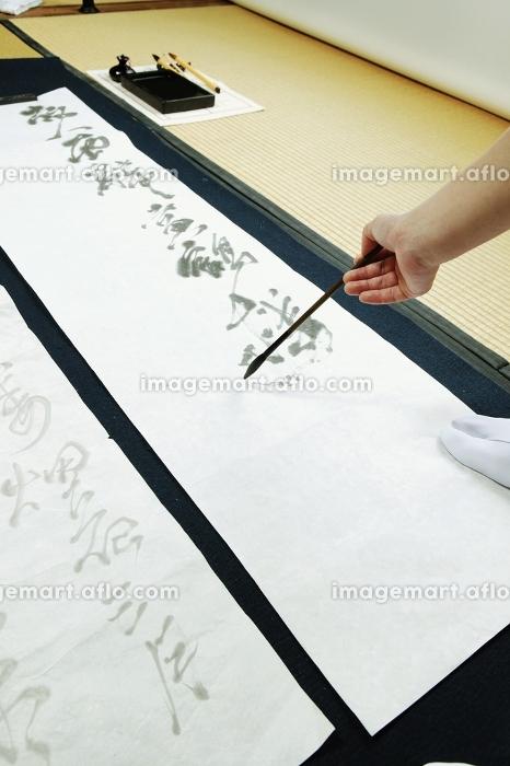 書き初めをする女性の販売画像