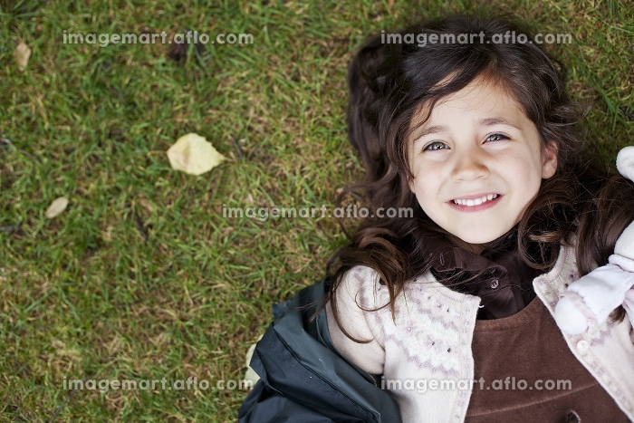Girl laying in grass outdoorsの販売画像